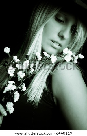 woman portrait with flower, studio in dark - stock photo