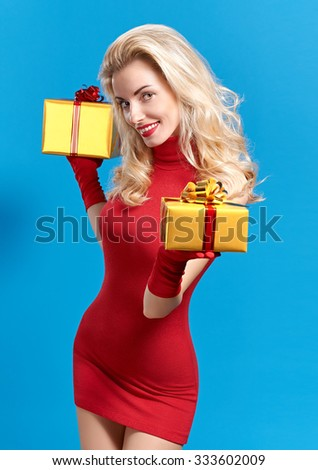 Woman portrait with gifts boxes beauty happy. Young curly playful blonde girl smiling in fashion red dress and gloves with gold presents on blue, people. Christmas vivid holiday, celebration copyspace - stock photo