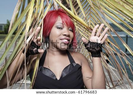 Woman posing among a palm frond - stock photo