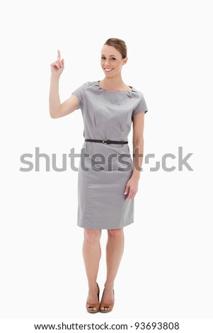 Woman posing in a dress showing something above with her hand against white background
