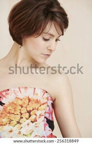 Woman posing in glamorous dress, looking down - stock photo