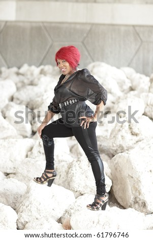 Woman posing on a rock formation - stock photo