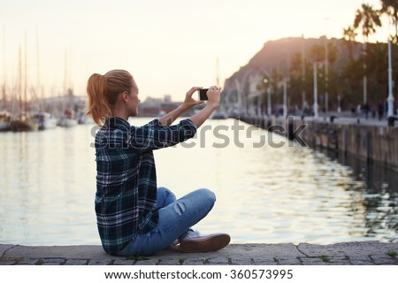 Woman posing while photographing herself on mobile phone for chat with friends in summer weekend, hipster girl enjoying her travel while making photo of beautiful landscape with cell telephone camera - stock photo