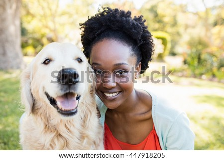 Woman posing with a dog at park