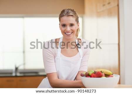 Woman posing with a fruit basket in her kitchen - stock photo