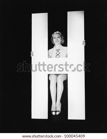 Woman posing with huge letter H - stock photo