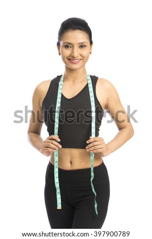 Woman posing with measuring tape over a white background - stock photo