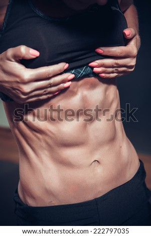 Woman posing with perfect abdomen muscles  - stock photo