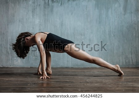 woman posing yoga asana in studio
