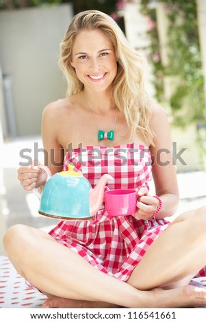 Woman Pouring Cup Of Tea - stock photo