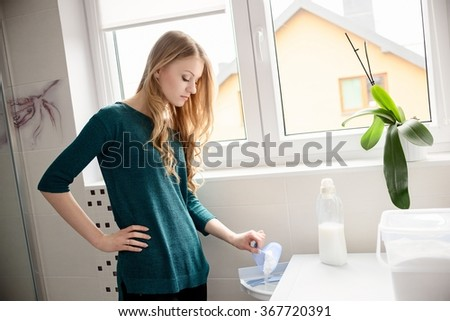 Woman pouring detergent into the washing machine in the bathroom