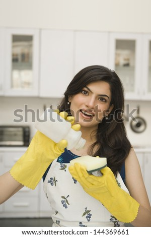 Woman pouring liquid soap on a sponge - stock photo