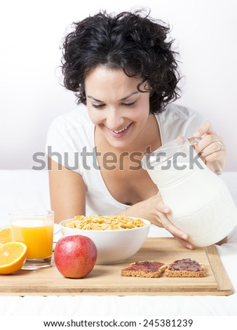 Woman pouring milk into bowl of cereals to breakfast. Happy beautiful young married woman having breakfast of milk, cereals, orange juice, toasts. Concept of nutrition and diet. Concept of marriage. - stock photo