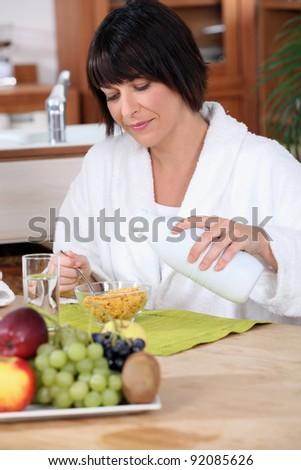 Woman pouring milk onto cornflakes - stock photo