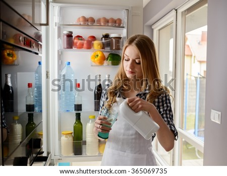 woman pouring milk while standing near from the refrigerator. Dressed in a plaid shirt and white apron - stock photo