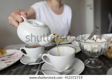 Woman pouring tea in cafe in the morning - stock photo