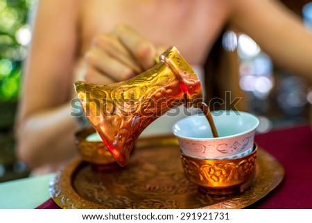 Woman pouring turkish coffee from traditional bronze cezve  in the restaurant - stock photo