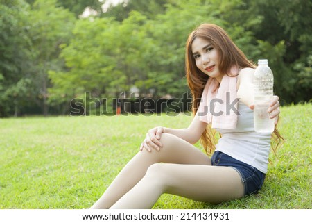 Woman pouring water from it. Sitting On the lawn in the park.