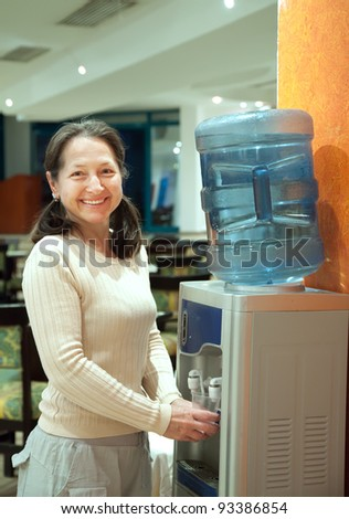 Woman pours   water from water cooler - stock photo