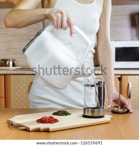 Woman pours water into french press