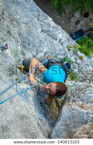 Woman practices in climbing at the rock in the Crimea mountains - stock photo