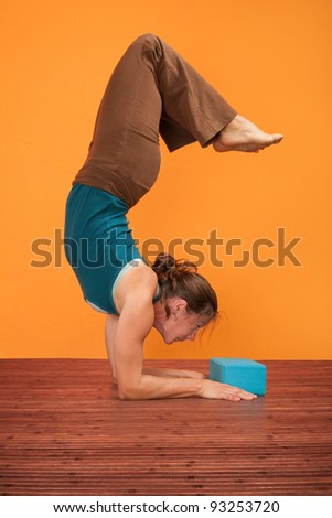 Woman practices Pincha Mayurasana over orange background - stock photo