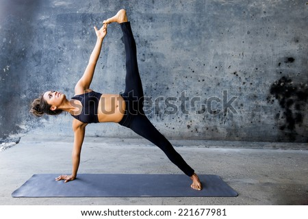 Woman practicing advanced yoga against a dark urban wall - stock photo