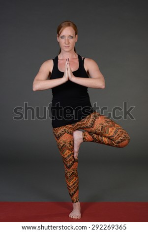 Woman practicing advanced yoga against  grey studio paper background. - stock photo