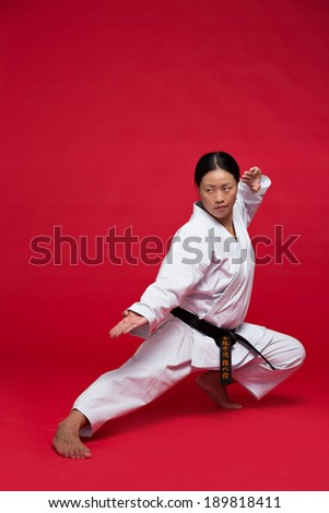 Woman practicing karate on red background - stock photo