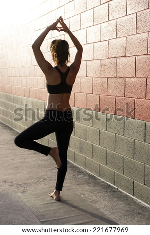 Woman practicing yoga against a brick wall - stock photo