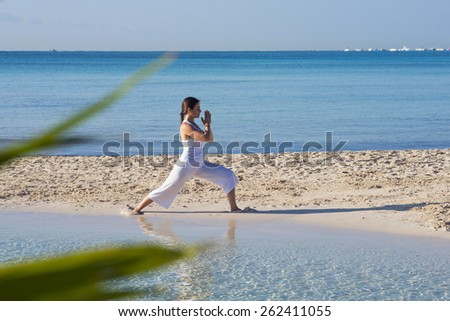 Woman practicing yoga at a tropical beach - stock photo