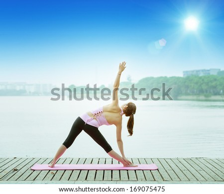 woman practicing yoga at seashore - stock photo