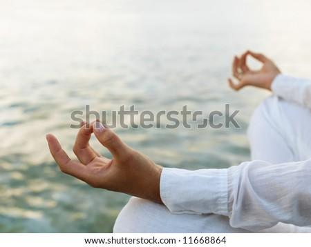 Woman practicing yoga at sunrise near the ocean - stock photo
