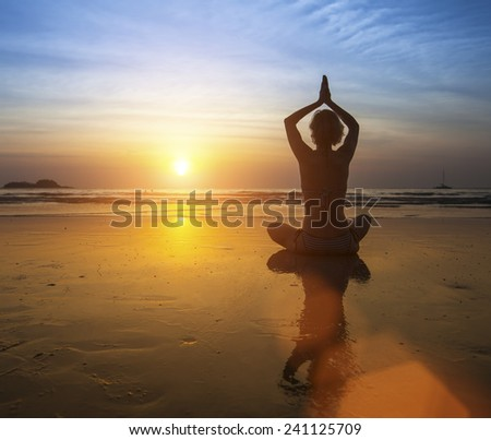 Woman practicing yoga at sunset on the beach. - stock photo