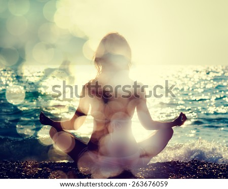 Woman Practicing Yoga by the Sea. Rear View. Double Exposure Filtered Photo with Bokeh. Soul Concept. - stock photo