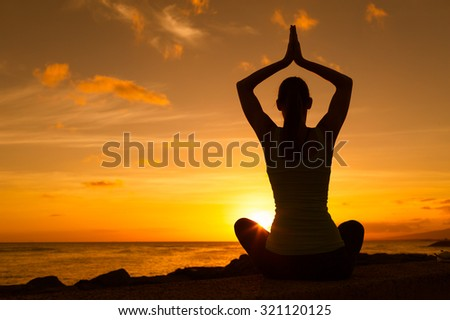 Woman practicing yoga in a sunset setting. - stock photo