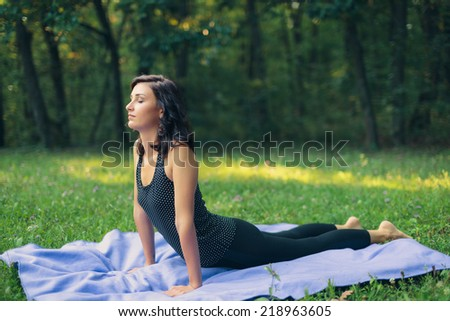 Woman Practicing Yoga in Cobra Pose with Eyes Closed Outdoors on Blanket in Tranquil Forest Setting - stock photo
