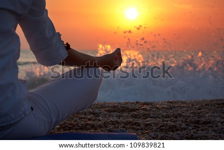 Woman Practicing Yoga near the Ocean at Sunset