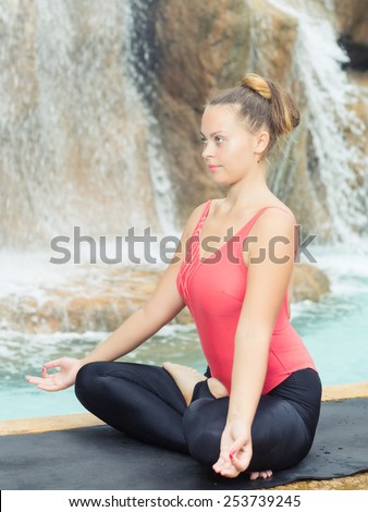 Woman practicing yoga near waterfall. Accomplished Pose. Siddhasana  - stock photo