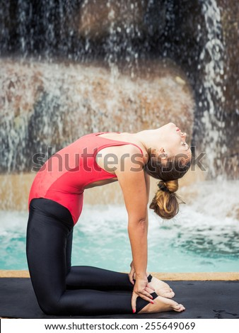 Woman practicing yoga near waterfall. Camel Pose. Ustrasana - stock photo