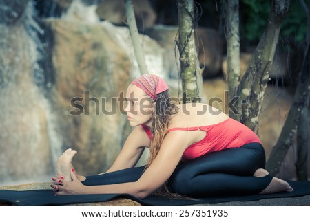 Woman practicing yoga near waterfall. Half hero stretch. Ardha Virasana - stock photo