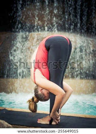 Woman practicing yoga near waterfall. Hands to Feet Pose. Padahastasana - stock photo
