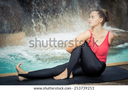 Woman practicing yoga near waterfall. Sage Twist. Marichyasana - stock photo