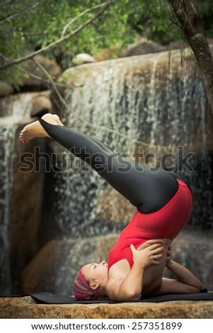 Woman practicing yoga near waterfall. Upside-Down Seal. Viparita Karani - stock photo