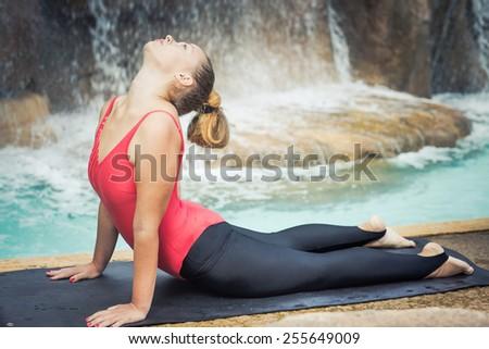 Woman practicing yoga near waterfall. Upward-Facing Dog. Urdhva mukha svanasana - stock photo
