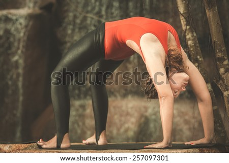Woman practicing yoga near waterfall. Wheel Pose. Chakrasana. Toned - stock photo