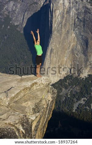 Woman practicing yoga on a mountain top, on a sunny  day. - stock photo