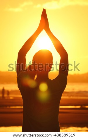 Woman practicing yoga on the beach at sunset - stock photo
