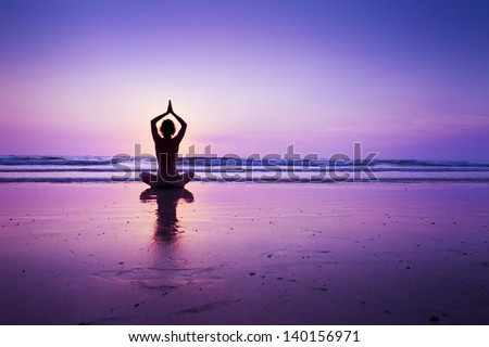 Woman practicing yoga on the beach at sunset in Koh Chang, Thailand - stock photo