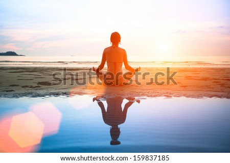 Woman practicing yoga on the ocean beach at sunset - stock photo